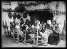 Photographie représentant une veillée rassemblant trois générations. Les femmes sont occupées à filer le chanvre ou le lin en vue de constituer des pelotes de fil destinées au tissage des vêtements ou du linge de maison.